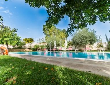 piscina con acqua salata riscaldata nel giardino dei carrubi a pochi passi dalla spiaggia di sabbia in Sicilia